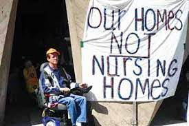male individual in wheel chair with sign saying Our Homes, Not Nursing Homes!