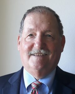 Picture of male individual with a mustache who is wearing a suit and tie
